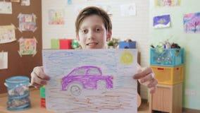 Leuke glimlachende jongen die beeld van de auto tonen die de camera bekijken stock videobeelden