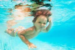 Leuke glimlachende jongen die onder water van pool zwemmen Stock Foto's