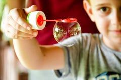 Leuke glimlachende jongen die zeepbels maken royalty-vrije stock afbeeldingen