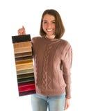 Leuke glimlachende vrouw in de stoffenmonsters van de sweaterholding Stock Afbeelding