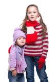 Leuke glimlachende zusters die kleurrijke gebreide die sweater, sjaal, hoed en handschoenen dragen op witte achtergrond wordt geï Stock Afbeeldingen