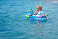 Leuke grappig gelukkig weinig jongen die in de watergolven op zee oceaan op een zonnige dag spelen stock afbeelding