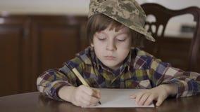 Leuke grappig weinig jongen in geruit overhemd en militaire hoed van zijn vader die een brievenzitting schrijven thuis bij de lij stock footage
