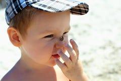 Leuke grappige babyjongen die insect op neus vangt stock afbeeldingen