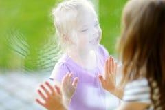 Leuke grappige kleine zusters playnig door een venster royalty-vrije stock fotografie
