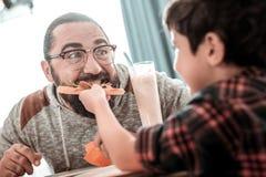 Leuke grootmoedige zoon die stuk van pizza geven aan zijn vader stock foto's