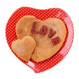 Leuke hart-vormige pannekoeken op rode plaat die op witte Hoogste mening wordt geïsoleerd stock foto's