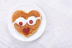 Leuke hart-vormige pannekoeken op rode plaat op witte lijst Hoogste mening stock foto