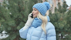 Leuke het glimlachen blondebesprekingen op de telefoon in openlucht dichtbij de spar stock videobeelden