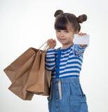 Leuke het glimlachen de korting van de kindholding witte kaart en het winkelen zakken in haar handen Jong geitje met creditcard M stock fotografie