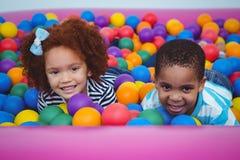 Leuke het glimlachen jonge geitjes in de pool van de sponsbal Stock Foto's