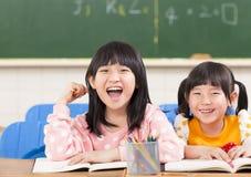 Leuke het glimlachen jonge geitjes in het klaslokaal royalty-vrije stock afbeeldingen