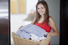 Leuke huisvrouwenvrouw die wasserij doet Stock Foto's