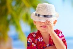 Leuke jong geitjejongen die zijn gezicht achter hoed verbergen Stock Afbeeldingen