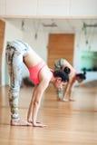 Leuke jonge en vrouw die alvorens bij een yoga uit te werken uitrekken zich opwarmen stock afbeeldingen