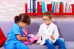 Leuke jonge geitjes die in artsen met stuk speelgoed instrumenten spelen Stock Afbeelding