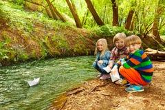 Leuke jonge geitjes die met document schepen bij rivieroever spelen Stock Foto's