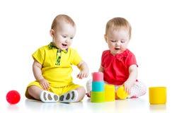 Leuke jonge geitjes die met kleurenspeelgoed spelen Kinderenmeisje Stock Foto's