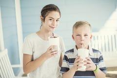 Leuke jonge geitjes die milkshaken of op smaak gebrachte dranken samen drinken stock fotografie
