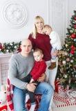 Leuke jonge geitjes en hun prachtige ouders die zich dichtbij de Kerstboom verenigen Royalty-vrije Stock Foto