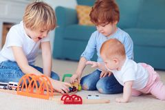 Leuke jonge geitjes, siblings die speelgoed samen op het tapijt spelen thuis stock afbeeldingen