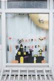 Leuke jonge geitjesdocument ambachtenvertoning bij het venster van het kinderdagverblijfhuis voor het vieren op 31 Oktober, Hallo Royalty-vrije Stock Afbeelding