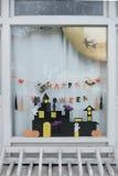 Leuke jonge geitjesdocument ambachtenvertoning bij het venster van het kinderdagverblijfhuis voor het vieren op 31 Oktober, Hallo Stock Afbeelding