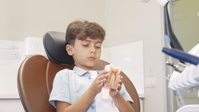 Leuke jonge jongen die aan de camera glimlachen, die tandmodel houden stock video