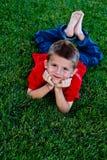 Leuke jonge jongen die in het gras ligt Royalty-vrije Stock Foto's