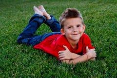 Leuke jonge jongen die in het gras ligt Stock Foto's