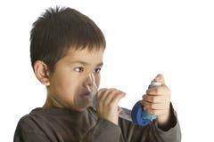 Leuke jonge jongen die zijn astmainhaleertoestel met behulp van Royalty-vrije Stock Foto