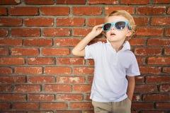 Leuke Jonge Kaukasische Jongen in Zonnebril tegen Bakstenen muur stock afbeeldingen