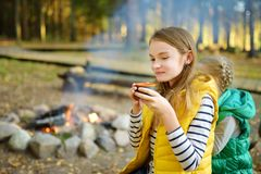 Leuke jonge meisje het drinken thee en roosterende heemst op stok bij vuur Kind die pret hebben bij kampbrand Het kamperen met ki stock foto