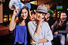 Leuke jonge meisjes die in Beierse hoeden bij de barachtergrond tijdens de viering van Oktoberfest glimlachen stock foto