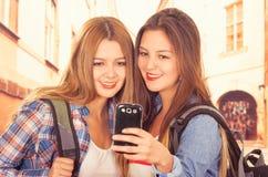 Leuke jonge modieuze meisjes die celtelefoon met behulp van Stock Foto