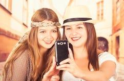 Leuke jonge modieuze meisjes die celtelefoon met behulp van Royalty-vrije Stock Foto