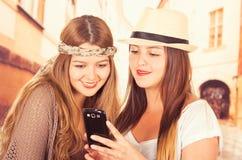 Leuke jonge modieuze meisjes die celtelefoon met behulp van Royalty-vrije Stock Fotografie