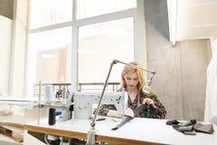 Leuke jonge naaister aan het werk aangaande een professionele naaimachine in een lichte salon die kleren ontwerpen royalty-vrije stock afbeelding