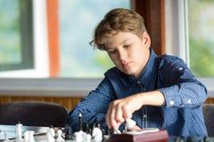 Leuke jonge slimme jongen in spelenschaak op de opleiding vóór de toernooien De hand maakt een beweging op schaakbord het kamp va stock afbeelding