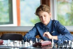 Leuke jonge slimme jongen in spelenschaak op de opleiding vóór de toernooien De hand maakt een beweging op schaakbord het kamp va stock afbeeldingen
