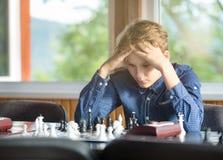 Leuke jonge slimme jongen in spelenschaak op de opleiding vóór de toernooien De hand maakt een beweging op schaakbord het kamp va royalty-vrije stock fotografie