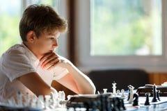 Leuke jonge slimme jongen in spelenschaak op de opleiding vóór de toernooien De hand maakt een beweging op schaakbord het kamp va stock foto