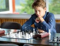 Leuke jonge slimme jongen in spelenschaak op de opleiding vóór de toernooien De hand maakt een beweging op schaakbord het kamp va stock fotografie