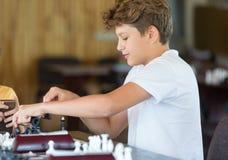 Leuke jonge slimme jongen in spelenschaak op de opleiding vóór de toernooien De hand maakt een beweging op schaakbord het kamp va stock foto's