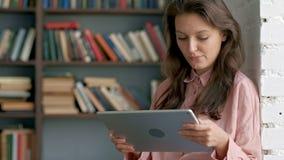 Leuke jonge student die een tabletcomputer in een bibliotheek met behulp van stock video