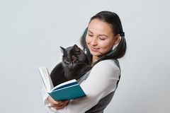 Leuke jonge studente met een grappige kat in haar wapens die een boek lezen op lichte achtergrond stock foto's