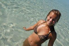Leuke jonge tiener die zich in water bij strand bevindt royalty-vrije stock foto