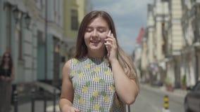 Leuke jonge vrouw die rond de oude Europese stad lopen, die op de telefoon spreken, die haar wapens golven Vrije tijd van gelukki stock footage