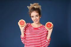 Leuke jonge vrouw met de helften van grapefruit op kleurenachtergrond stock afbeelding