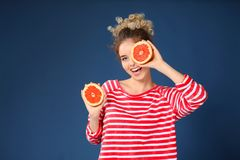 Leuke jonge vrouw met de helften van grapefruit op kleurenachtergrond royalty-vrije stock foto's